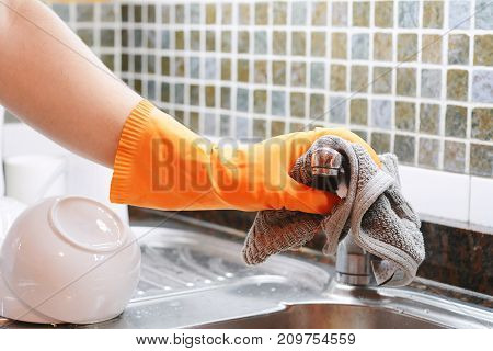Hand With Gloves Wiping Stainless Steel Sink With Cloth