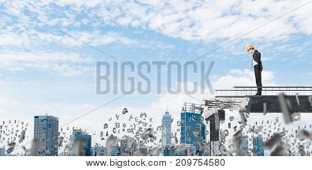 Young engineer in suit and helmet looking down while standing among flying letters on broken bridge with cityscape on background. 3D rendering.