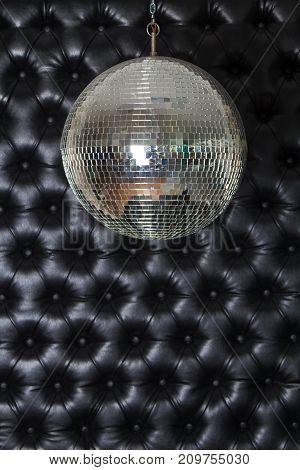 Silver shiny disco-ball on the black sofa background.