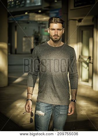 Handsome young man standing indoor, inside big building, looking at camera with confident stare