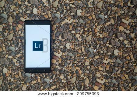Los Angeles, USA, october 18, 2017: Adobe photoshop lightroom logo on smartphone on background of small stones
