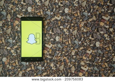 Los Angeles, USA, october 18, 2017: Snapchat logo on smartphone on background of small stones