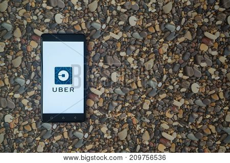 Los Angeles, USA, october 18, 2017: Uber logo on smartphone on background of small stones
