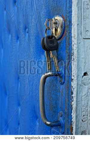 key in the keyhole on the blue old door