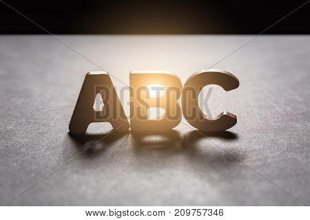 Letters Abc Of Wooden Letters On A Dark Texture With A Black Background With Backlight. Lighting Eff