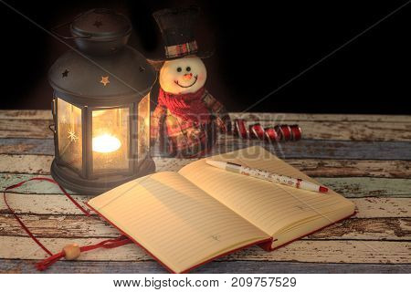 Journal and pen with snowman in lantern light in darkness