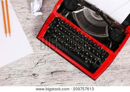 Vintage red typewriter maschine on the wooden table