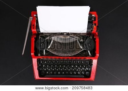 Photo of vintage red typewriter on the table with paper onblack background