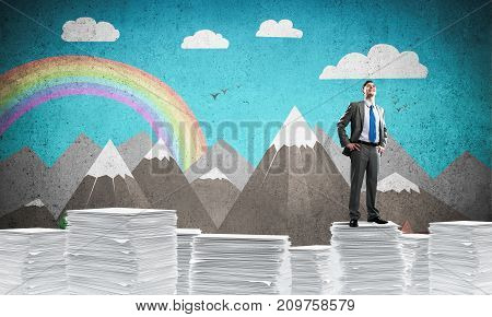 Confident businessman in suit standing on pile of documents with drawn landscape on background. Mixed media.