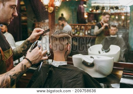 A Man Getting Trendy Haircut At Barber Shop. Male Hairstylist In Tattoos Serving Client.