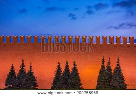 Wall of red brick with backlight silhouettes of christmas trees against the wall background blue sky at dusk. Wall of the Moscow Kremlin, Russia.