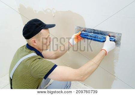 A worker is plastering a wall in a apartment from the bottom up.