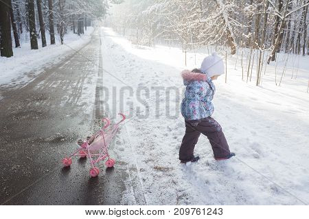 Walking little girl in warm winter clothing among snowdrifts outdoors
