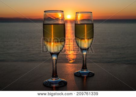 Romantic evening, sunset, two wineglasses, sun path on the water between two wineglasses with wine.