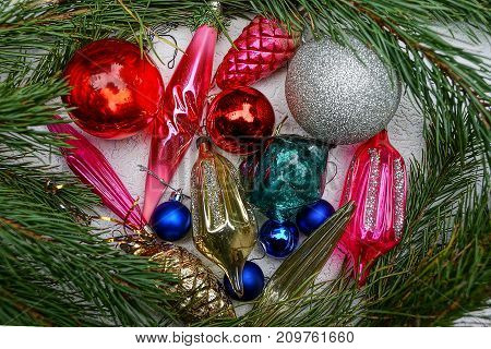 New Year's bright colored toys and pine branches on a gray background