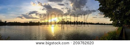 Sunset and silhouette buildings reflects on water at Jacqueline Kennedy Onassis reservoir in panorama