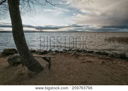 wooden bench on the bank of the lake on a rainy autumn decline