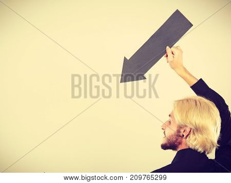 Planning directions choices concept. Man holding black arrow pointing left down. Indoor shot on light background