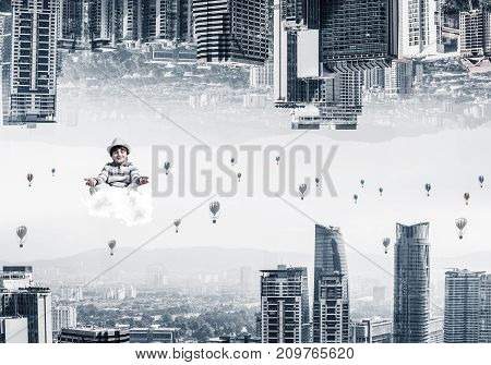 Young boy keeping eyes closed and looking concentrated while meditating on cloud among flying aerostats and between two urban worlds.