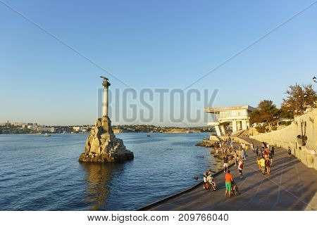 Tourists Take Pictures Near The Monument To The Scuttled Ships In The Sevastopol Bay At Sunset
