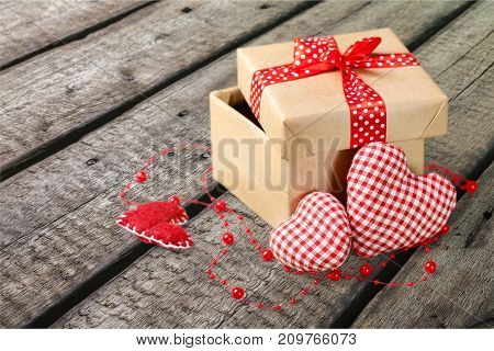 Red gift box two hearts table background