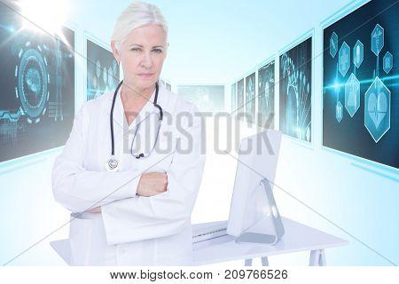 Portrait of confident female doctor standing by desk against 3D blue vignette background