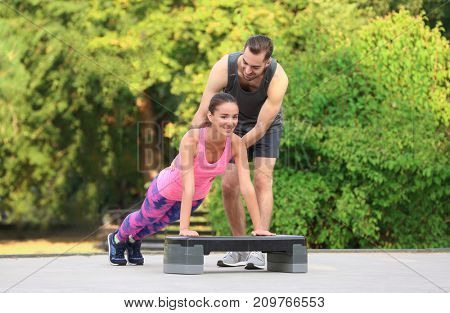 Young woman exercising with personal trainer on sports ground