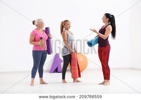 Women with yoga mats indoors