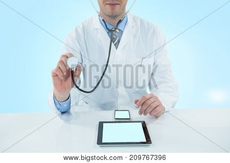 Doctor examining with 3D stethscope against blue vignette background