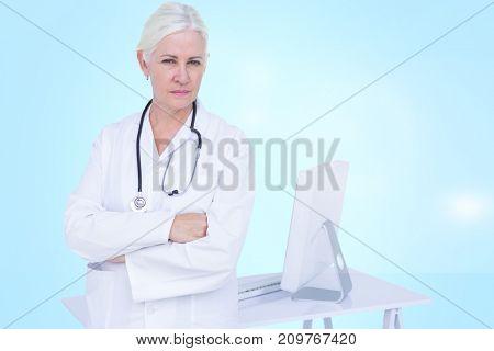 Portrait of confident female doctor standing by desk against blue vignette background