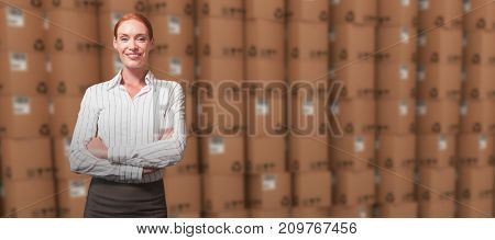 Female manager with arms crossed in warehouse against open cardboard box by pile of boxes