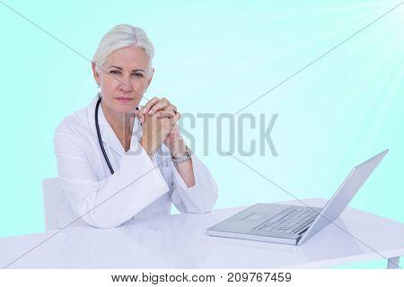 Portrait of confident female doctor with 3D laptop on desk against blue vignette background