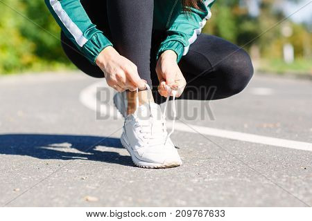 Young athletic girl ties up shoelaces on sneakers