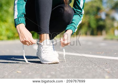 Horisontal photo young athletic girl ties up shoelaces on sneakers