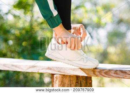 Photo of athlitic girl ties up sneakers