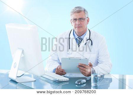 Portrait of confident male doctor sitting at 3D computer desk against blue vignette background