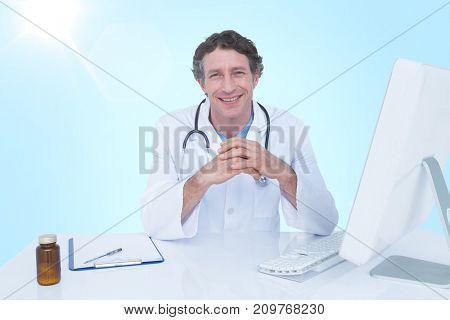Portrait of happy doctor against blue vignette background