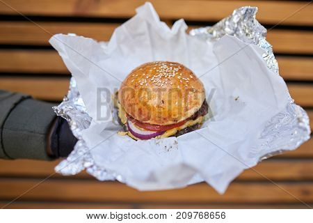 Fresh juicy burger with beef, cheese, tomato, salad, majo, onion in male hand in a black gloves on a wooden background. Close-up of burger. Food concept.