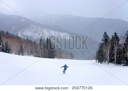 Snowboarder going down the slope at snowy forest resort