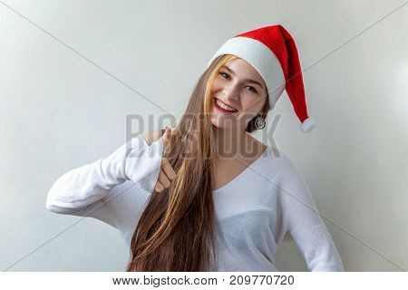Christmas woman showing thumb up. Santa girl smiling in red Santa hat. Beautiful happy Caucasian woman isolated on white background