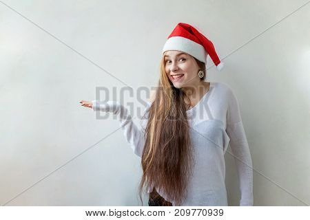 Christmas woman showing blank area for sign or copyspase. Santa girl smiling in red Santa hat. Beautiful happy Caucasian woman isolated on white background
