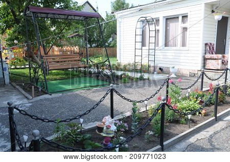 resting area with swing in garden designing for cottage houses among flowers