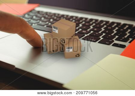 High angle view of cardboard 3D boxes against cropped hand using laptop