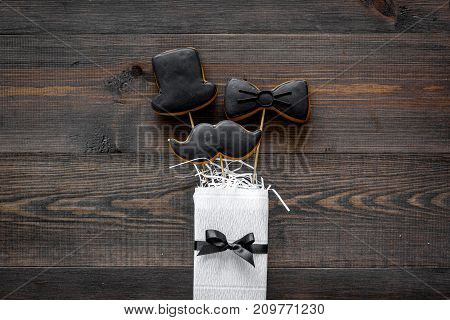 Happy Father's day present cards. Black tie, mustache and hat cookies and gift. Wooden desk background top view mockup