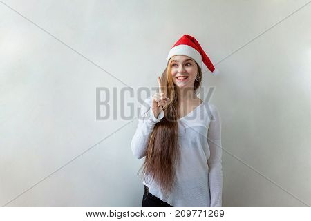 Santa girl have an idea in red Santa hat. Christmas Santa hat isolated woman portrait . Smiling happy girl on white background.