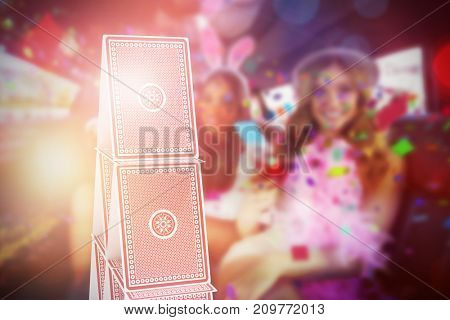 Composite 3D image of portrait of female friends drinking cocktails against 3d image of card tower