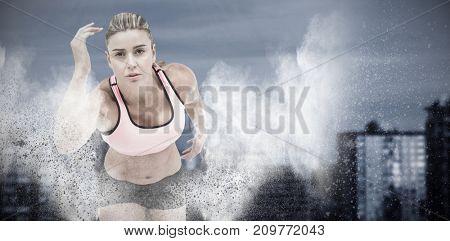 Female athlete on the start line against splashing of dust powder