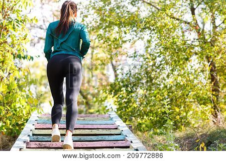 Photo of athletic girl climbs the stairs. White sneakers, black leggings and sexy legs. Horizontal photo