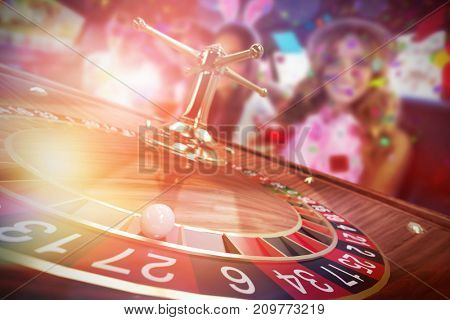 Portrait of female friends drinking cocktails against 3d image of ball on wooden roulette wheel