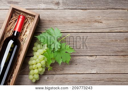 Wine bottle and grapes on wooden table. Top view with space for your text